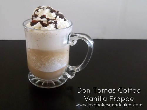 Vanilla Frappe with whipped cream and chocolate drizzle in glass mug.