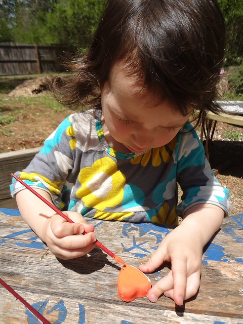 Painting an orange plaster heart.