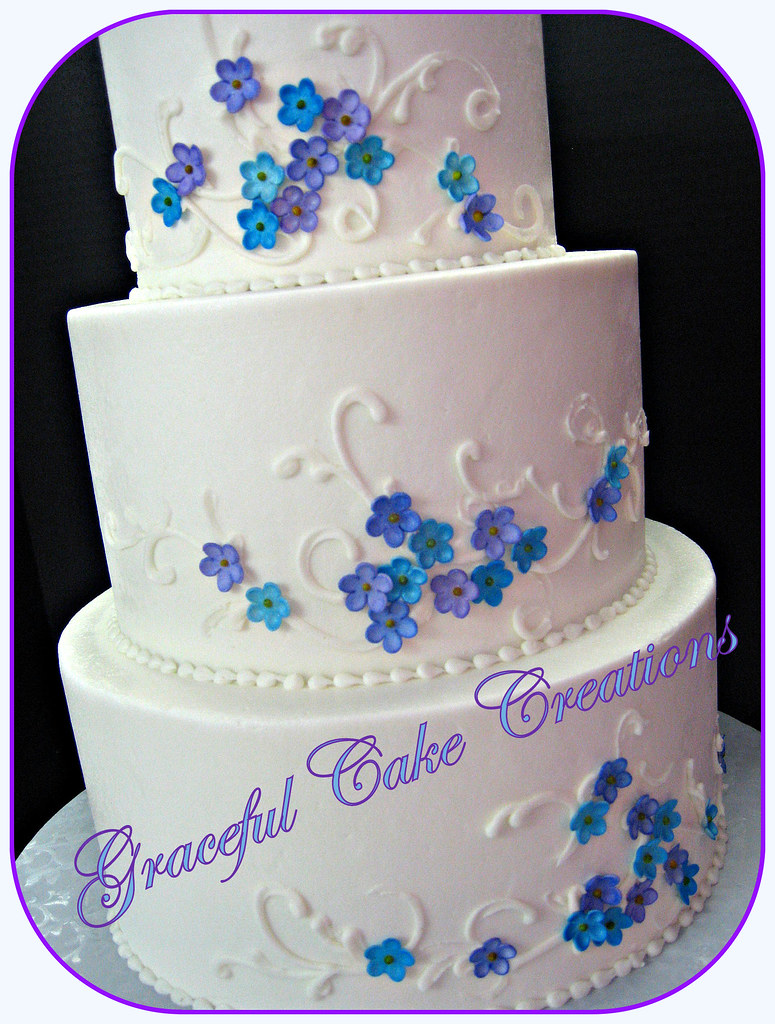 White Buttercream Wedding Cake with Purple and Blue Flowers - a ...