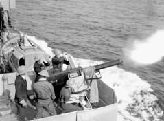 Unidentified personnel firing a two-pounder anti-aircraft gun aboard HMCS Assiniboine... / Des membres du personnel non identifiés tirent un coup de canon antiaérien de deux livres à bord du NCSM Assiniboine...