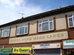 "The first floor of a building above a parade of shops.  Some of the shopfronts are visible, including a dry cleaners and a money transfer office.  Set into the concrete above the shopfronts are the words ""BONZA HOME MADE CAKES""."