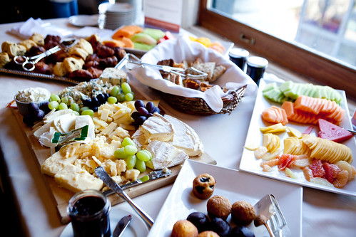 Breakfast spread of various cheeses, sliced fruit, croissants and muffins