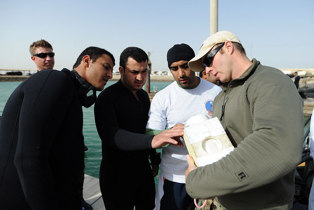 Explosive Ordnance Disposal Technician 2nd Class Jakob Isbrandtsen, assigned to Commander, Task Group 56.1, Explosive Ordnance Disposal Mobile Unit 2, describes an underwater sonar to Qatar Emiri Navy Special Forces divers during a interoperability exerci