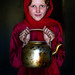 Portrait of an afghan girl with pale skin wearing red clothes and holding a tea pot, Badakhshan province, Khandood, Afghanistan by Eric Lafforgue