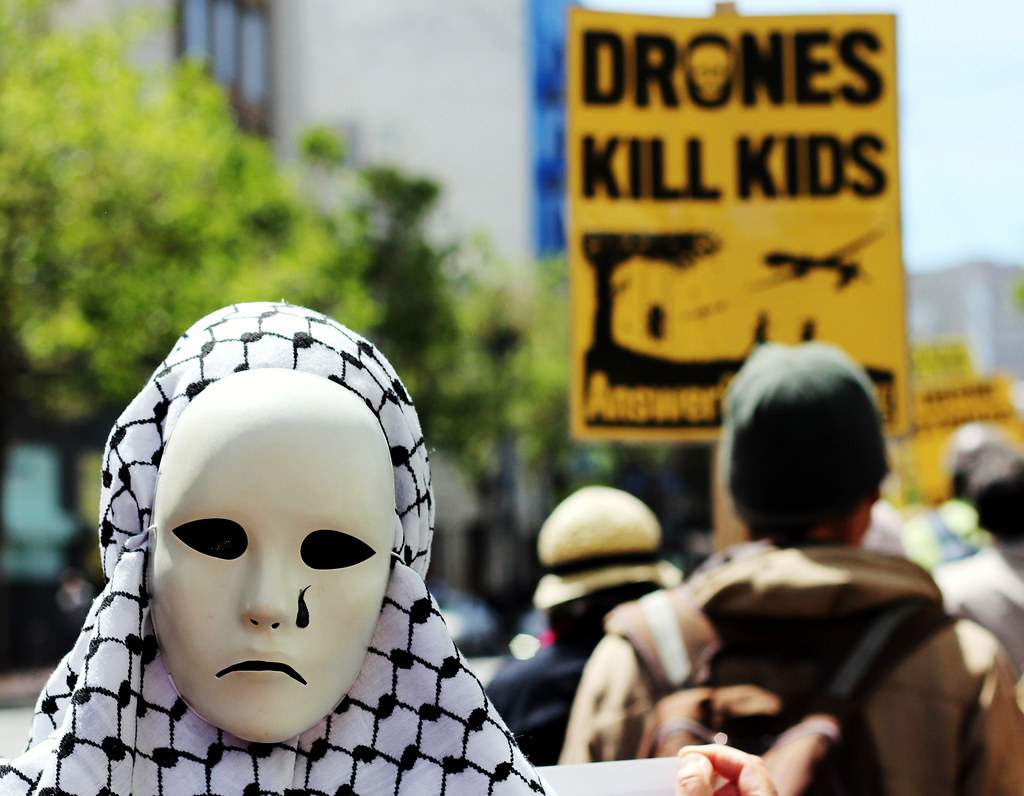 A protester wears a mask and marches down Market Street to Union Plaza in San Francisco. The march was part of a protest against the U.S. drone strikes being used around the world. Photo by Gavin McIntyre / Special to Xpress