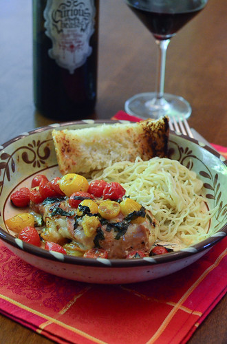 Chicken Caprese served with noodles and garlic bread.