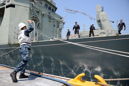Boatswain's Mate 3rd Class Steven Muller, assigned to USS McCampbell (DDG 85) tosses a line as the Royal Australian Navy arrives