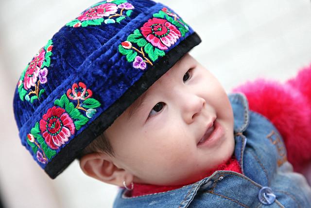 Little girl wearing flower embroiderd doppa for adults, Kumul (Hami) ハミ、大人用のクムルドッパを被った少女