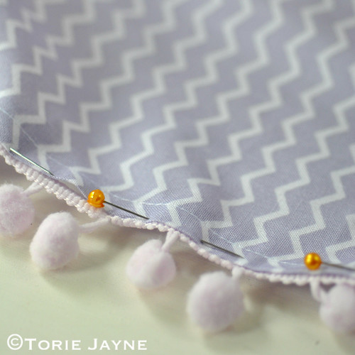 Pin pom pom trim to hem of tablecloth