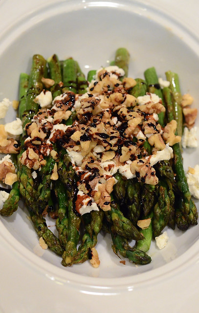 A serving dish with Roasted Asparagus with Balsamic, Goat Cheese & Toasted Walnuts.