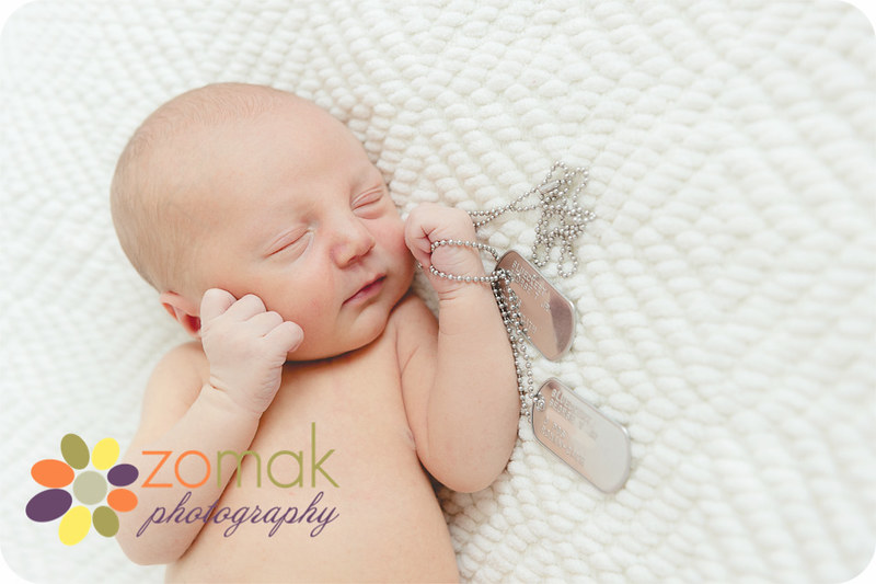 Newborn baby holds his father's dog tags during his photo shoot.