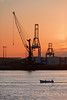 fishing boat in industrial harbor with cranes at sunset