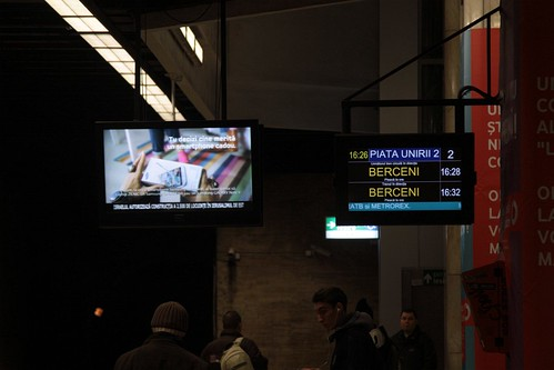Next train display beside an advertising screen at Piata Unirii station