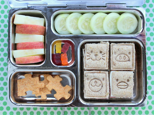 PlanetBox school lunch - square animal face sandwiches, cucumber slices, apple slices, organic gummy bears, puzzle piece crackers