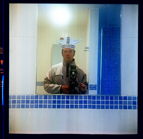 reflected self-portrait with Voigtlander Brilliant camera and Viking headgear by pho-Tony