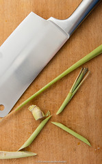 Lemongrass chopping on wooden chopping board.