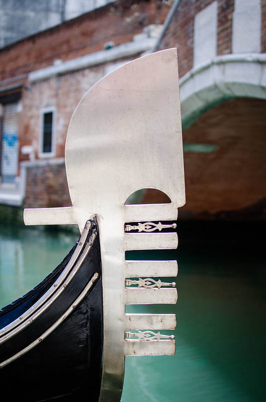 A gondola ornament at rest along a small canal in Venice.