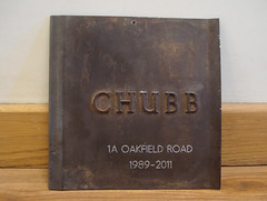 "A square piece of dark metal of about 20cm on each side, propped up against an interior wall.  The word ""CHUBB"" is embossed on it in large letters, and it has been engraved with the words: ""1A Oakfield Road / 1989–2011""."