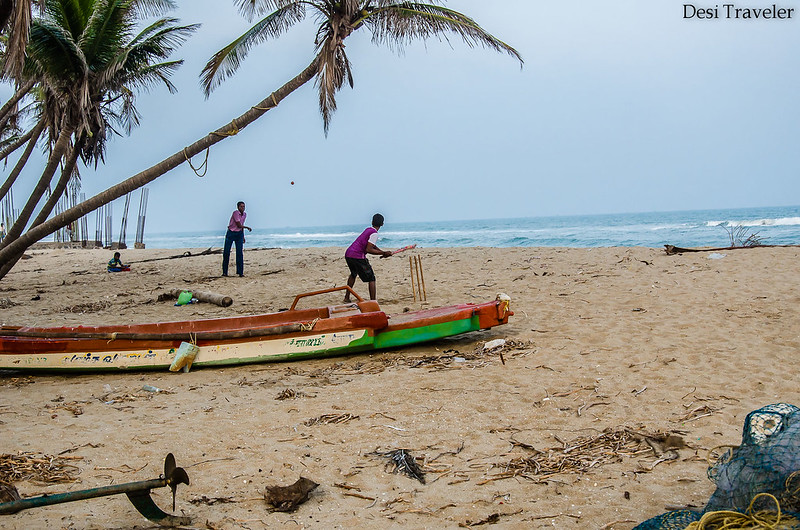 boys playing beach cricket in a fishing village in pondicherry