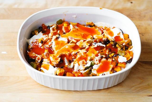 Pour enchilada sauce over the sour cream in the casserole dish