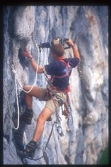 Greg Bolting to a cave on the cliff face Image