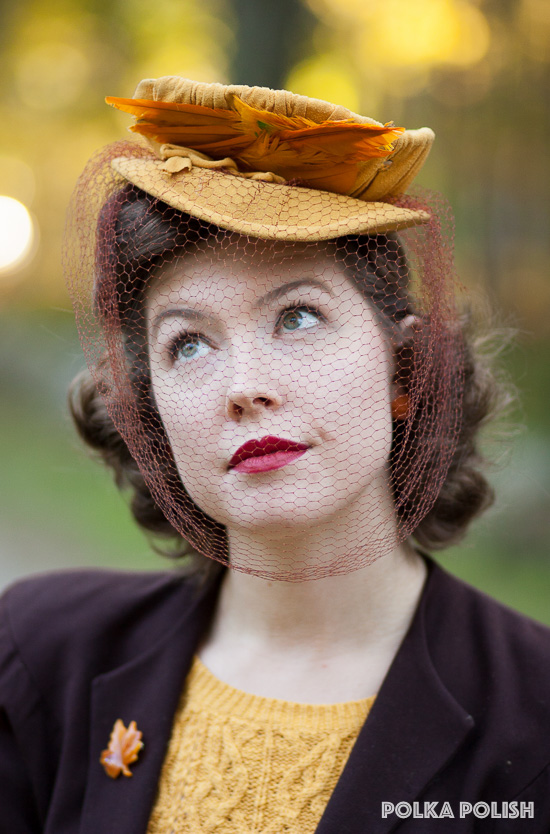 A vintage 1940s tilt hat in yellow jersey topped with two golden pads of feathers and a huge rust-colored veil