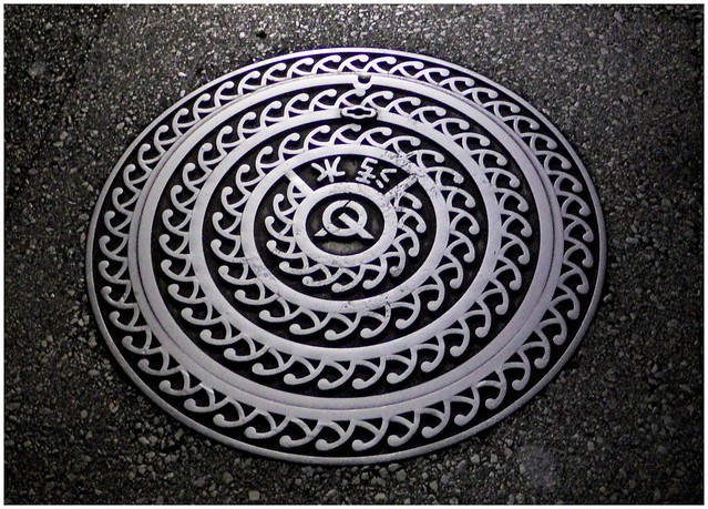 THE ETERNAL WAVES OF CRASHING SURF CYCLE ENDLESSLY UPON THE SILVER SEA -- A MANHOLE COVER UNDER A STREET LIGHT