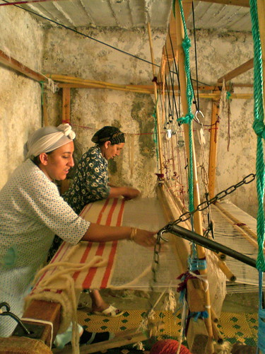 Jamila and Rachida weave wool blankets on a horizontal loom