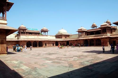 Über einen Hof in Fatehpur Sikri laufen Grüppchen von Touristen