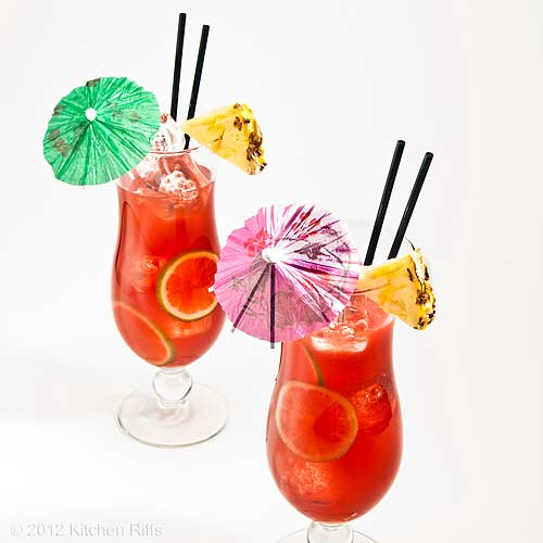 Planter's Punch Cocktails with Pineapple Garnish and Umbrellas, White Background