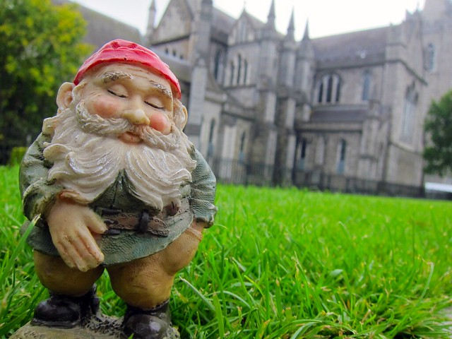 Close-up of a little gnome statue in the foreground with the cathedral in the background.