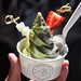 Cup of matcha and black sesame soft serve swirl, matcha powder, condensed milk drizzle, strawberry and mochi