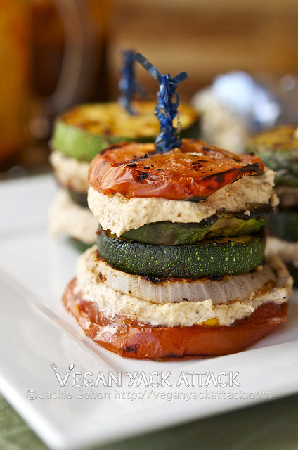 Stacked grilled veggies with layers of smoky almond cream on a white plate