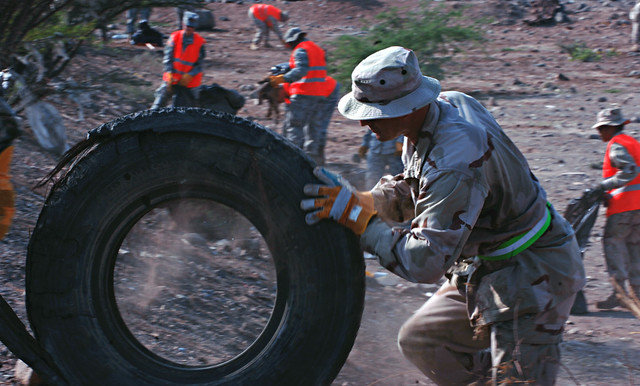 DJIBOUTI, Djibouti (Nov. 5, 2011) - U.S. Navy Senior Chief Petty Officer Reese Ritter, Combined Joint Task Force - Horn of Africa surgeon cell senior enlisted leader, rolls a tire up a hill outside the perimeter of Camp Lemonnier, Djibouti. Ritter joined more than 200 service members from the camp for the Djibouti Pride Initiative. The effort brought together locals as well as Djiboutian, coalition and Camp Lemonnier service members in collecting and removing hundreds of bags of trash from the area outside the camp. U.S. Air Force photo by Senior Airman Jarad A. Denton.