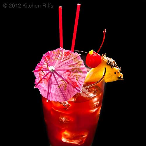 Singapore Sling Cocktail with Pineapple and Maraschino Chery Garnish, Black Background