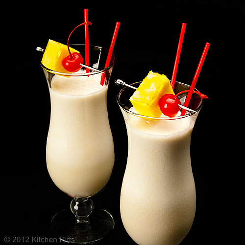 Piña Colada Cocktails with Pineapple and Maraschino Cherry Garnish, Black Background