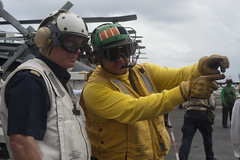 Swedish navy Rear Adm. Anders Grenstad, left, a member of the Neutral Nations Supervisory Commission, learns about flight operations from Lt. Steve Duran, during an overnight visit aboard the aircraft carrier USS George Washington (CVN 73).
