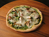homemade pesto pizza with spinach, mushrooms, onions and mozzarella