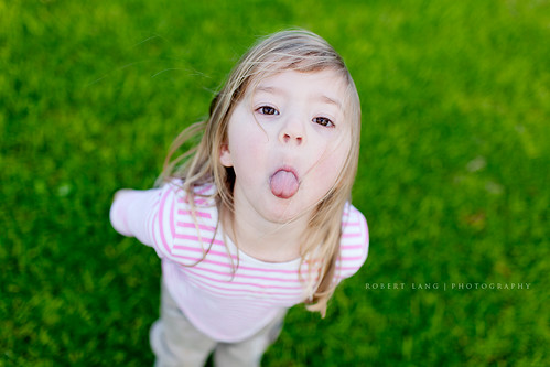 Young girl standing on grass poking tongue out, Australia