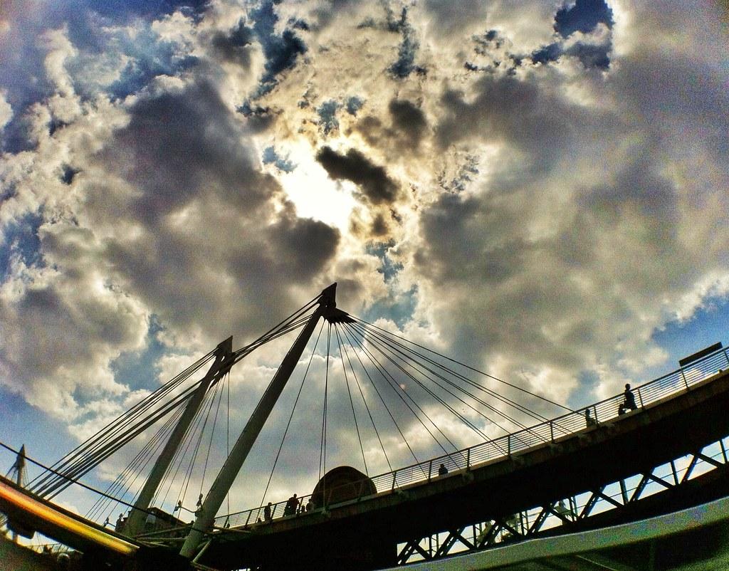 Under the sun, under the clouds, under the bridge where I sit