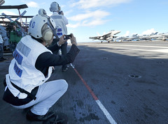 A Japanese visitor takes a picture of an arrested landing during flight operations aboard USS George Washington, Aug. 22. (U.S. Navy photo by Mass Communication Specialist 3rd Class Stephanie Smith)