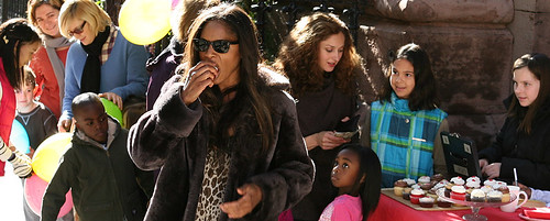 Alison McDonald wearing sunglasses and eating an apple in a crowd