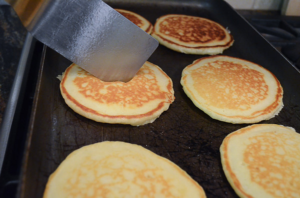 A spatula poking the center of the pancake to check if it is done cooking.
