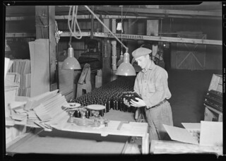 Whitall Tatum packer testing bottles before putting them into the carton at the lower right hand corner, March 1937