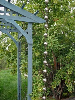 Stainless steel gazing globe rain chain beside entry arbour
