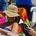 Three ladies reading on the beach with Kentucky Derby-like hats