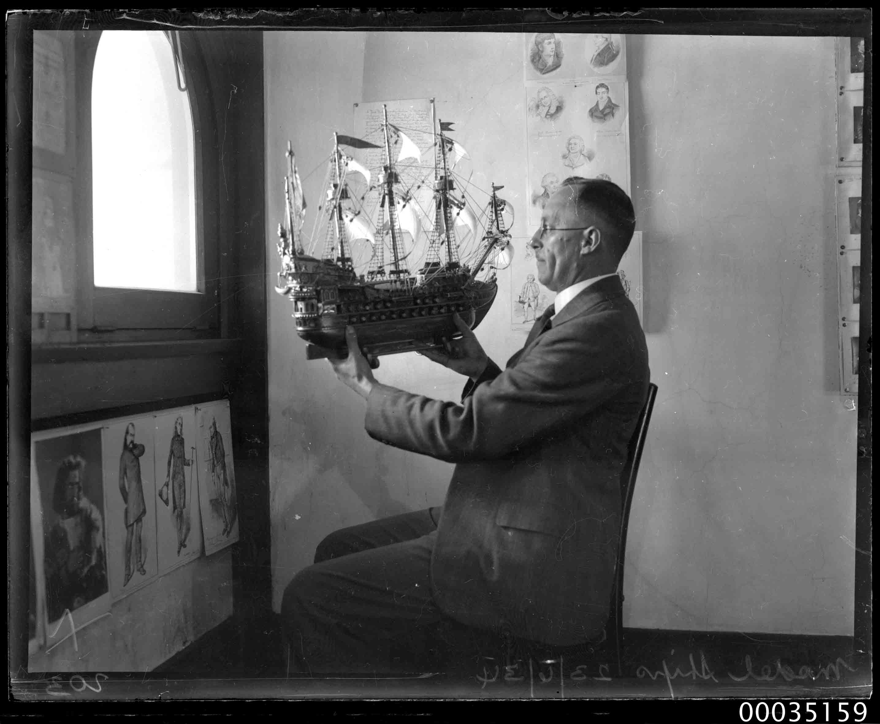 Man holding up a model of 16th century galleon, 23 June 1934
