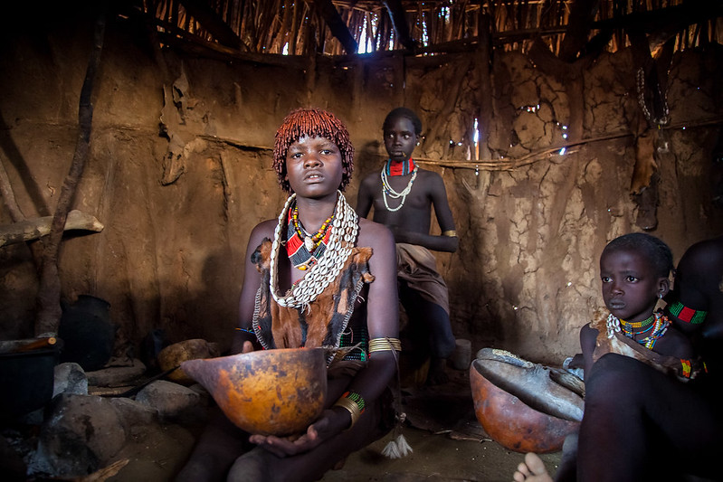 Hamer tribe girl prepares the drink coffee' inside in hut, omo valley, ethiopia.