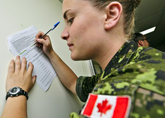 PACIFIC OCEAN (July 8, 2012) Canadian Army Pvt. Jill Macdonald fills out arrival paperwork upon joining Pacific Partnership 2012 aboard USNS Mercy. (Photo by Kristopher Radder)