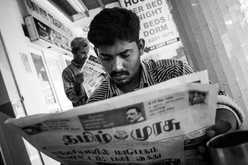 Man reading newspaper at a coffeeshop in Little India, Singapore